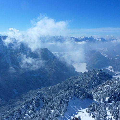 gleitschirmfliegen über verschneiter winterlandschaft im allgäu.