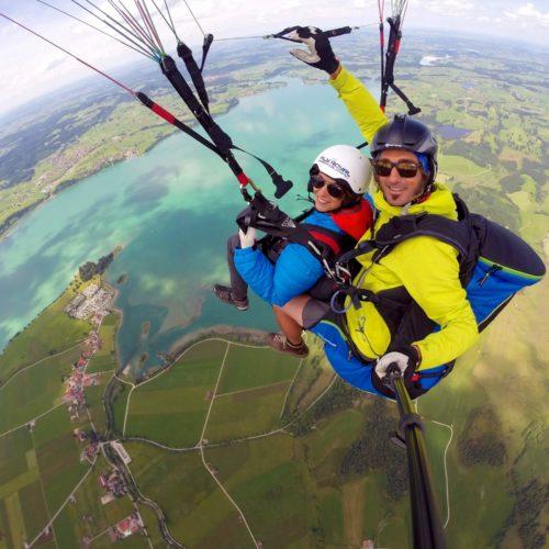 paragliding tandemflug über dem forggensee bei füssen im allgäu.