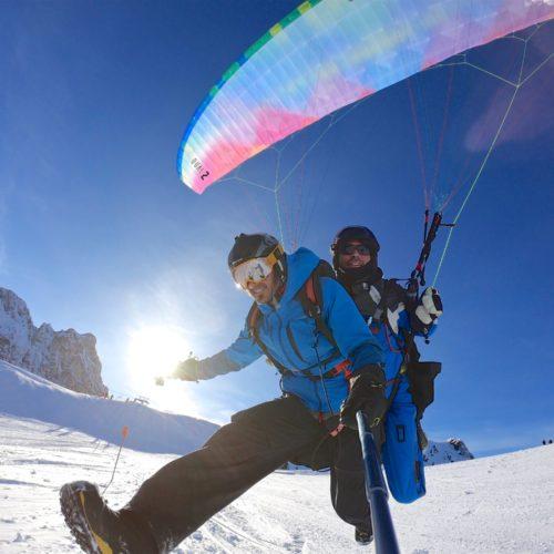 pilot und passagier starten zu einem gleitschirm tandemflug im winter.